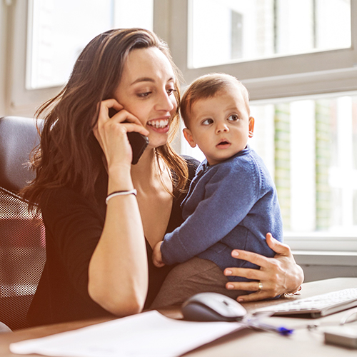 mother on cellphone holding baby at her desk