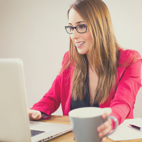 Woman with coffee mug working with her laptop